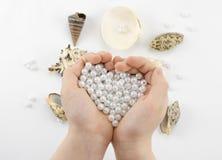 Χέρια με τις χάντρες και τα θαλασσινά κοχύλια μαργαριταριών Στοκ Φωτογραφίες