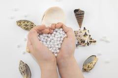Χέρια με τις χάντρες και τα θαλασσινά κοχύλια μαργαριταριών Στοκ Εικόνες