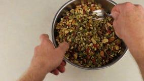 Χέρια με το δίκρανο που αναμιγνύει το μίγμα καρυδιών και φρούτων απόθεμα βίντεο