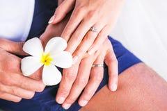 Χέρια με το γαμήλιο δαχτυλίδι και τα λουλούδια ή Plumeria Frangipani Στοκ φωτογραφίες με δικαίωμα ελεύθερης χρήσης
