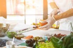 Χέρια με το καρότο περικοπών μαχαιριών Στοκ φωτογραφία με δικαίωμα ελεύθερης χρήσης