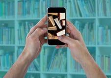 Χέρια με το τηλέφωνο που παρουσιάζει μόνιμα βιβλία ενάντια στο μουτζουρωμένο ράφι με την επικάλυψη κιρκιριών Στοκ εικόνες με δικαίωμα ελεύθερης χρήσης