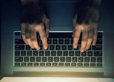 Χέρια με το lap-top επάνω από τη δακτυλογράφηση τη νύχτα Στοκ Εικόνες