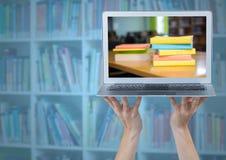 Χέρια με το lap-top που παρουσιάζει σωρό βιβλίων ενάντια στο μουτζουρωμένο ράφι με την μπλε επικάλυψη Στοκ Φωτογραφίες