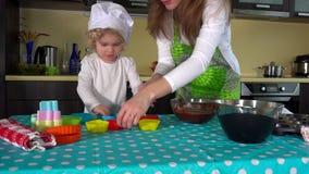 Χέρια μητέρων και κορών που προετοιμάζουν τη ζύμη για το φλυτζάνι-κέικ στον πίνακα απόθεμα βίντεο