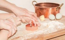 Χέρια μητέρων και παιδιών που προετοιμάζουν τα μπισκότα σε έναν πίνακα με το αλεύρι, αυγά, φόρμα χαλκού Στοκ Φωτογραφίες