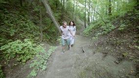 Χέρια μιας αγάπης ζευγών εκμετάλλευσης που περπατούν κατά μήκος μιας πορείας στο δάσος απόθεμα βίντεο