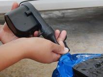 Χέρια μιας γυναίκας και που χρησιμοποιούν τη μίνι αεραντλία, που συνδέεται που κρατούν με το βούλωμα αυτοκινήτων, για να διογκώσε στοκ φωτογραφία με δικαίωμα ελεύθερης χρήσης