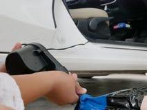 Χέρια μιας γυναίκας και που χρησιμοποιούν τη μίνι αεραντλία, που συνδέεται που κρατούν με το βούλωμα αυτοκινήτων, για να διογκώσε στοκ εικόνες με δικαίωμα ελεύθερης χρήσης