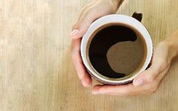 Χέρια μιας γυναίκας που κρατά ένα μεγάλο φλιτζάνι του καφέ Ξύλινη ανασκόπηση Τοπ όψη διάστημα αντιγράφων Στοκ Φωτογραφίες
