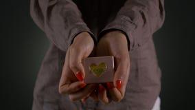 Χέρια μιας γυναίκας που κρατά και που παρουσιάζει μικρό κιβώτιο δώρων απόθεμα βίντεο
