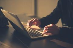 Χέρια μιας εκτελεστικής εργασίας στο lap-top του στο γραφείο στοκ φωτογραφία