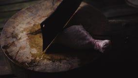 Χέρια μιας ηλικιωμένης κυρίας που τεμαχίζει το φρέσκο κοτόπουλο σε έναν ξύλινο τέμνοντα πίνακα απόθεμα βίντεο