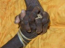 Χέρια μιας ηλικιωμένης κυρίας που ενώνεται στο κίτρινο φόρεμά της Στοκ Φωτογραφία