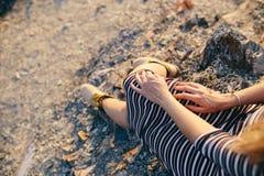 Χέρια μιας νέας γυναίκας σε ένα ριγωτό φόρεμα και κίτρινες μπότες Στοκ Φωτογραφία