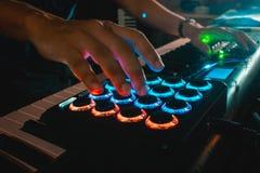 Χέρια μουσικών που παίζουν έναν ελεγκτή μαξιλαριών του Midi στοκ εικόνες