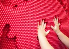 Χέρια μωρών που κάνουν handprint στο κόκκινο παιχνίδι καρφιτσών Στοκ Εικόνες
