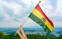 Χέρια νεαρών άνδρων ` s που κυματίζουν υπερήφανα τη εθνική σημαία της Βολιβίας στον ουρανό, τρισδιάστατη απόδοση μερών Στοκ φωτογραφίες με δικαίωμα ελεύθερης χρήσης