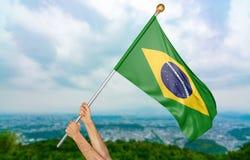 Χέρια νεαρών άνδρων ` s που κυματίζουν υπερήφανα τη εθνική σημαία της Βραζιλίας στον ουρανό, τρισδιάστατη απόδοση μερών Στοκ φωτογραφία με δικαίωμα ελεύθερης χρήσης