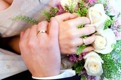 Χέρια νυφών και νεόνυμφων και ανθοδέσμη της νύφης στοκ εικόνες