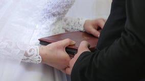 Χέρια νυφών και νεόνυμφων στη Βίβλο Η νύφη και ο νεόνυμφος τοποθετούν τα χέρια τους στη Βίβλο στους όρκους ανταλλαγής φιλμ μικρού μήκους