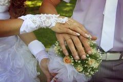 Χέρια νυφών και νεόνυμφων ` s με τα χρυσά δαχτυλίδια Στοκ Εικόνες