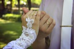 Χέρια νυφών και νεόνυμφων ` s με τα χρυσά δαχτυλίδια Στοκ Εικόνα