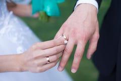 Χέρια νυφών κινηματογραφήσεων σε πρώτο πλάνο και νεόνυμφων ` s με τα γαμήλια δαχτυλίδια Στοκ φωτογραφία με δικαίωμα ελεύθερης χρήσης