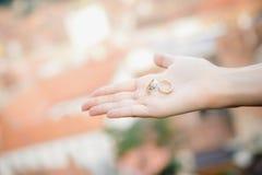 Χέρια νυφών που κρατούν τα δαχτυλίδια γάμου Στοκ εικόνες με δικαίωμα ελεύθερης χρήσης
