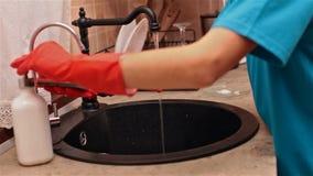 Χέρια παιδιών με τα λαστιχένια γάντια που προετοιμάζονται να πλύνει τα πιάτα απόθεμα βίντεο