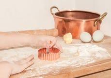 Χέρια παιδιών που κάνουν pasrty με τη ζύμη, αλεύρι, κομμάτι του βουτύρου, ε Στοκ Φωτογραφίες