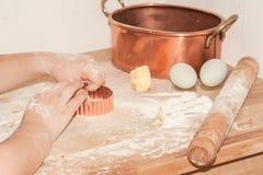 Χέρια παιδιών που κάνουν pasrty με τη ζύμη, αλεύρι, κομμάτι του βουτύρου, ε Στοκ εικόνα με δικαίωμα ελεύθερης χρήσης