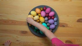 Χέρια παιδιών που παίρνουν τα πολύχρωμα αυγά Πάσχας από ένα πιάτο απόθεμα βίντεο