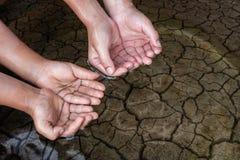 Χέρια παιδιών στο ξηρό χώμα Στοκ Εικόνα