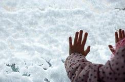 Χέρια παιδιών ` s στο χιονισμένο γυαλί στοκ εικόνες