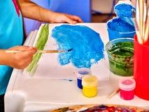 Χέρια παιδιών με τη ζωγραφική βουρτσών στον πίνακα μέσα Στοκ φωτογραφία με δικαίωμα ελεύθερης χρήσης