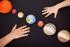 Χέρια παιδιών με τους πλανήτες του ηλιακού συστήματος Στοκ Φωτογραφία