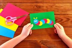 Χέρια παιδιών που κρατούν την κάμπια εγγράφου applique Φύλλα εγγράφου, ψαλίδι σε ένα καφετί ξύλινο υπόβαθρο Στοκ φωτογραφία με δικαίωμα ελεύθερης χρήσης