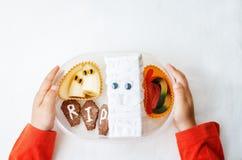 Χέρια παιδιών που κρατούν το καλαθάκι με φαγητό για αποκριές Στοκ εικόνα με δικαίωμα ελεύθερης χρήσης
