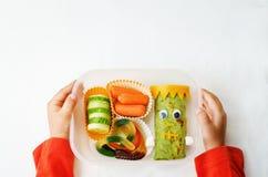 Χέρια παιδιών που κρατούν το καλαθάκι με φαγητό για αποκριές Στοκ Φωτογραφίες