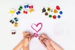 Χέρια παιδιών ` s που χρωματίζουν μια καρδιά Στοκ Εικόνες