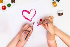 Χέρια παιδιών ` s που χρωματίζουν μια καρδιά Στοκ Εικόνα