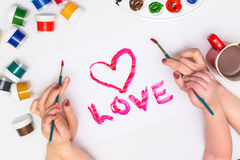 Χέρια παιδιών ` s που χρωματίζουν μια καρδιά Στοκ Φωτογραφία