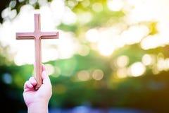 Χέρια παλαμών προσώπων για να κρατήσει τον ιερό σταυρό, crucifix για να λατρεψει Στοκ Εικόνες