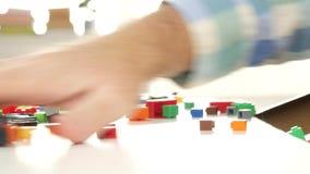 Χέρια παππούδων που ξαναβάζουν τούβλα χρωματισμένα στα κιβώτιο παιχνιδιών για τις κατασκευές απόθεμα βίντεο