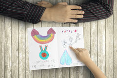 Χέρια πατέρων και παιδιών με τη ευχετήρια κάρτα στοκ φωτογραφίες