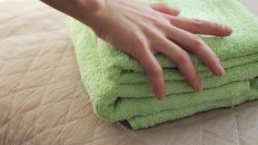 Χέρια που βάζουν τις πράσινες πετσέτες απόθεμα βίντεο