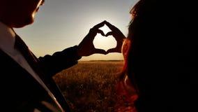 Χέρια που διαμορφώνουν μια μορφή καρδιών με τη σκιαγραφία ηλιοβασιλέματος απόθεμα βίντεο