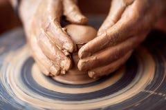 Χέρια που λειτουργούν στη ρόδα αγγειοπλαστικής Στοκ Φωτογραφίες