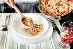 Χέρια που εξυπηρετούν σε ένα πιάτο quinoa stew στοκ εικόνες